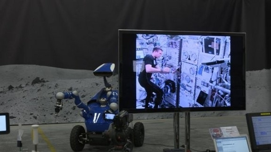 Andreas Mogensen, aboard the International Space Station, is visible here controlling the Interact rover as it prepared to place a metal peg into a hole.