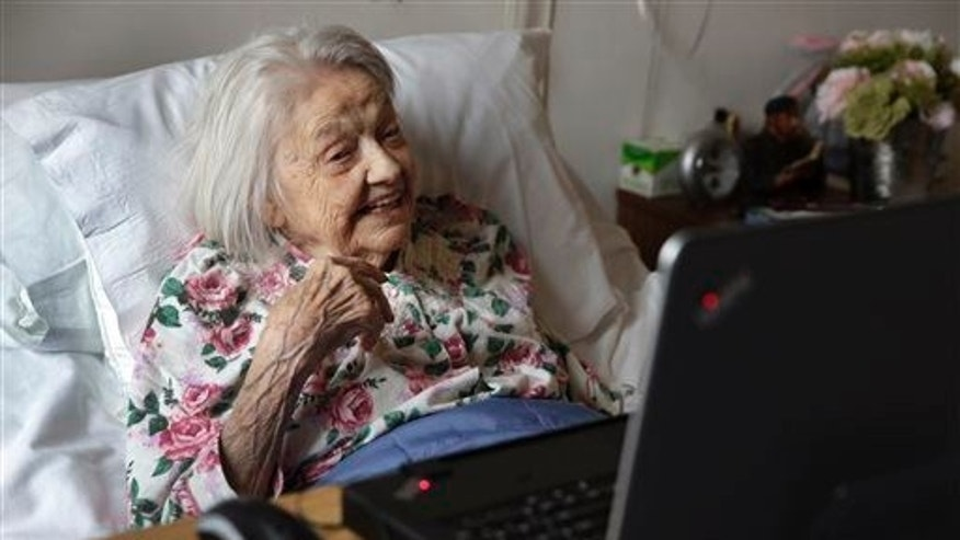Patient Louise Irving watches a laptop computer with her daughter's morning wake-up video playing, at The Hebrew Home of Riverdale, in New York, Wednesday, March 25, 2015. The nursing home in the Bronx has started a pilot program in which relatives record video messages for patients of Alzheimer's and other forms of dementia. The videos are played for them each morning to calm their agitation and reassure them about their surroundings and their routines.