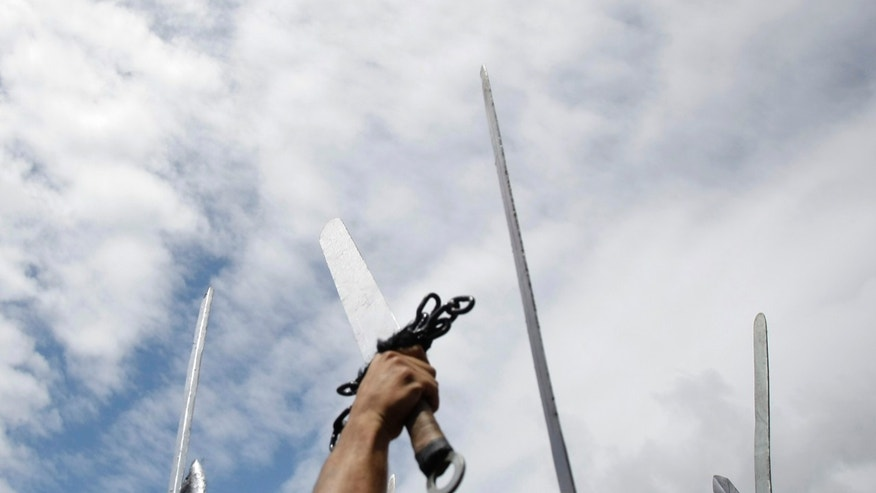 File photo - Participants dressed up as Vikings raise their swords as they take part in the annual Viking festival of Catoira in north-western Spain Aug. 7, 2011.