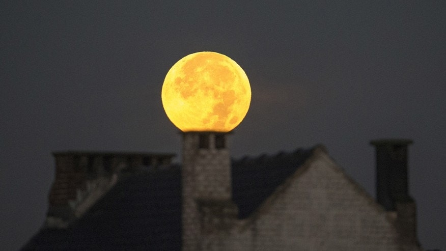 "File photo - A supermoon appears behind a house after a total ""supermoon"" lunar eclipse in Brussels Sept. 28, 2015. (REUTERS/Yves Herman)"