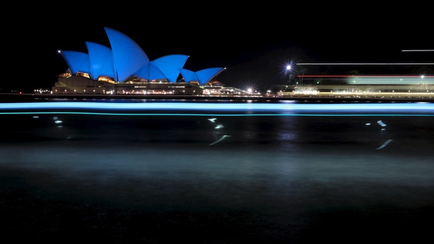 Ferries create long exposure streaks of light as they sail past the Sydney Opera House illuminated in a shade of blue Oct. 24. (REUTERS/Jason Reed)