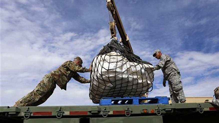 Sgt. James Ray and Staff Sgt. Noe Amador secure the remains of a Pentaceratops, Thursday, Oct. 29, 2015, to a flatbed trailer in the Bisti-De-Na-Zin Wilderness area south of Farmington, N.M. The fossils are encapsulated in heavy plaster jackets.  (Jon Austria/The Daily Times via AP)