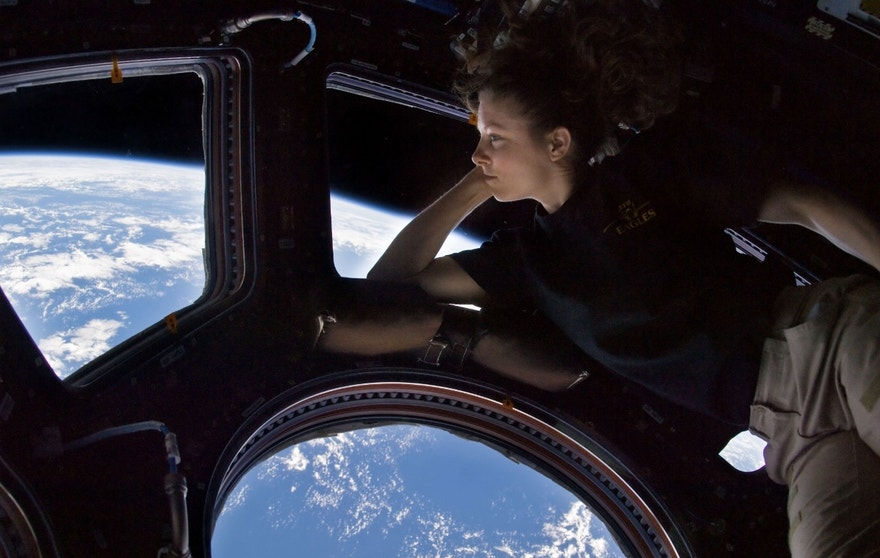 NASA astronaut Tracy Caldwell Dyson, Expedition 24 flight engineer, looks through a window in the Cupola of the International Space Station. A blue and white part of Earth and the blackness of space are visible through the windows.
