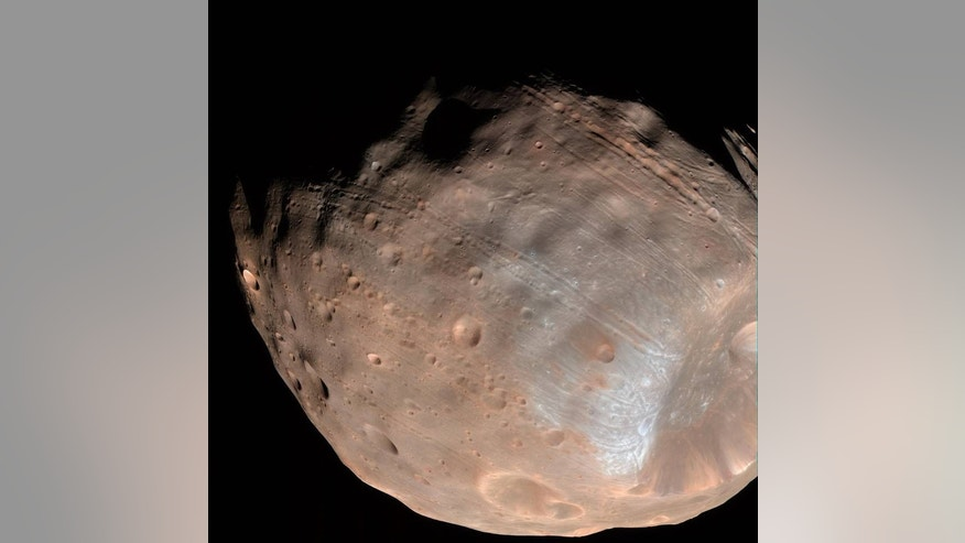 New modeling indicates that the grooves on Mars' moon Phobos could be produced by tidal forces – the mutual gravitational pull of the planet and the moon. Initially, scientists had thought the grooves were created by the massive impact that made Stickney crater (lower right). (NASA/JPL-Caltech/University of Arizona)