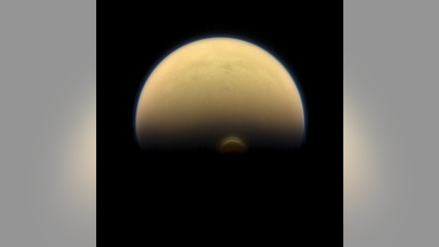 "As winter sets in at Titan's south pole, a cloud system called the south polar vortex (small, bright ""button"") has been forming, as seen in this 2013 image."