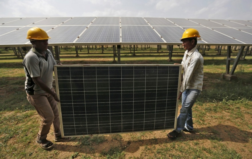 Workers carry a damaged photovoltaic panel inside a solar power plant in Gujarat, India, July 2, 2015. India's $100 billion push into solar energy over the next decade will be driven by foreign players as uncompetitive local manufacturers fall by the wayside, no longer protected by government restrictions on the sector. REUTERS/Amit Dave - RTX1IR4N