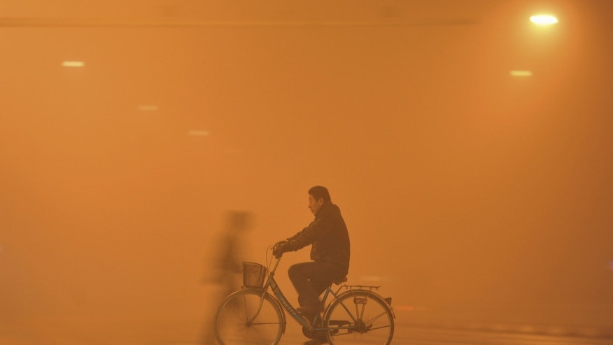 A man rides his bicycle across a street amid heavy haze in Fuyang, Anhui province, China, November 30, 2015. Heavy smog and thick fog engulfed many parts of northern and eastern China on Monday, local media reported. REUTERS/Stringer CHINA OUT. NO COMMERCIAL OR EDITORIAL SALES IN CHINA. - RTX1WFOM