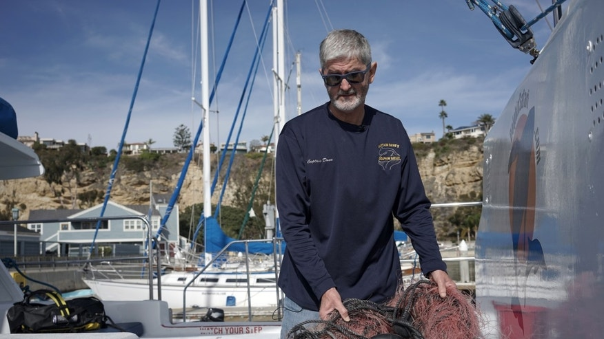 In this Monday, Nov. 30, 2015 photo, Capt. David Anderson of Captain Dave's Dolphin and Whale Watching Safari in Dana Point, Calif., shows a net a whale was found entangled in. Anderson was among the first to realize whale entanglements were a serious problem when his tours kept running into distressed whales. This year alone, more than 60 entangled whales have been spotted along the coast, a more than 400 percent spike over normal and a pattern that began in 2014. (AP Photo/Christine Armario)