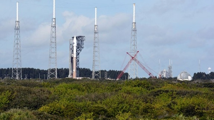 A new crew access tower rises beside a United Launch Alliance Atlas V rocket as the modifications continue to Pad 39A for SpaceX Falcon rocket crewed launches in the background. The two launch pads are being readied to support commercial crew l