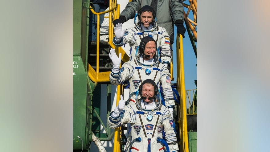 Russian cosmonaut Yuri Malenchenko (top), NASA astronaut Tim Kopra (center) and British astronaut Tim Peake of the European Space Agency wave farewell as they board their Soyuz rocket for a launch to the International Space Station on Dec. 15,
