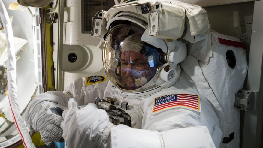 In this photo provided by NASA and posted on Twitter on Oct. 26, 2015, astronaut Scott Kelly tries on his spacesuit inside the U.S. Quest airlock of the International Space Station. NASA opened its astronaut-application website Monday, Dec. 14, 2015. It's accepting applications through Feb. 18, 2016. (NASA via AP)