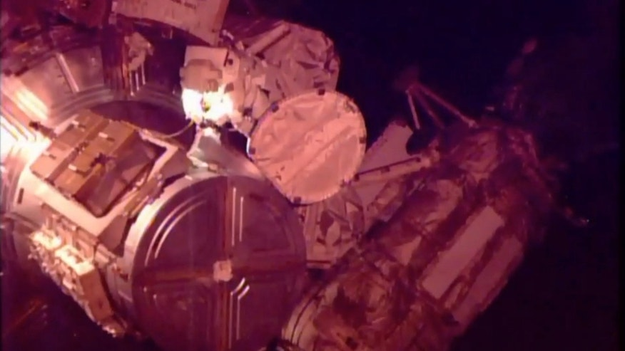 In this photo provided by NASA-TV, American astronaut Scott Kelly returns to the International Space Station at the end of a spacewalk in which he and fellow American Timothy Kopra helped move a stalled rail car back into place outside the space station, on Monday, Dec. 21, 2015. (NASA TV via AP)