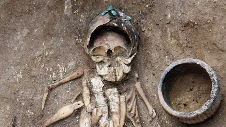 This infant lived around 4,500 years ago and was buried in a birchbark cradle with eight intricately carved figurines. The infant also wears headgear made from 11 copper plaques sewn together. (Yury Esin)