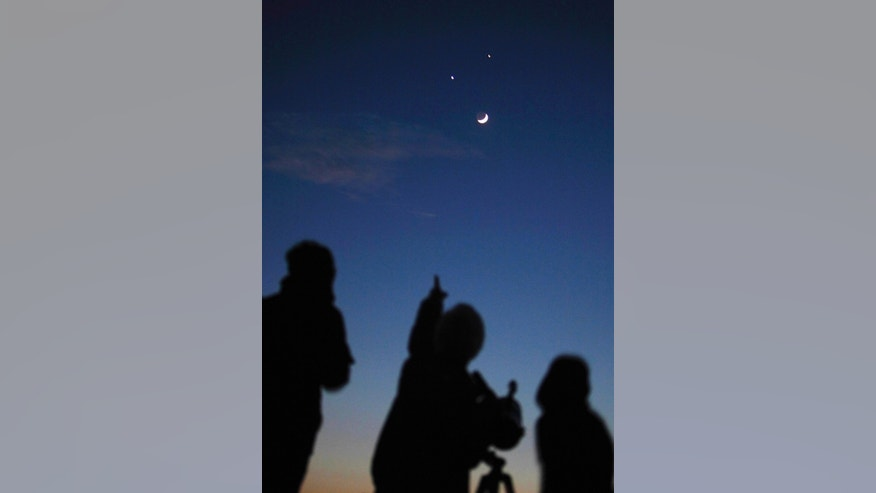 Star gazers look at the crescent moon below Jupiter (top) and Venus in Kathmandu December 1, 2008. (REUTERS/Gopal Chitrakar)