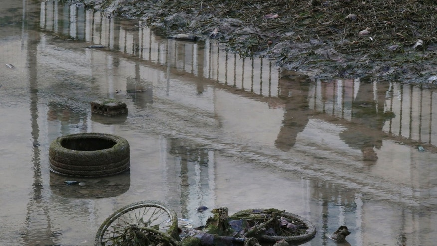 A bicycle and a tire are seen on the ground of the Canal Saint-Martin as the canal is drained for maintenance in Paris on Wednesday.