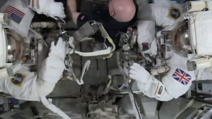 This photo taken from video provided by NASA shows astronaut Scott Kelly, center, help gather equipment for U.S. astronaut Tim Kopra, left, and British astronaut Tim Peake, as they prepare for a space walk at the International Space Station on Friday, Jan. 15, 2016. Peake will become the first Briton to walk in space when he ventures out of the International Space Station (ISS) (NASA via AP)