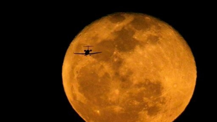 A jet is silhouetted by the rising waning moon on a landing approach at Phoenix's Sky Harbor International Airport on March 6, 2015.
