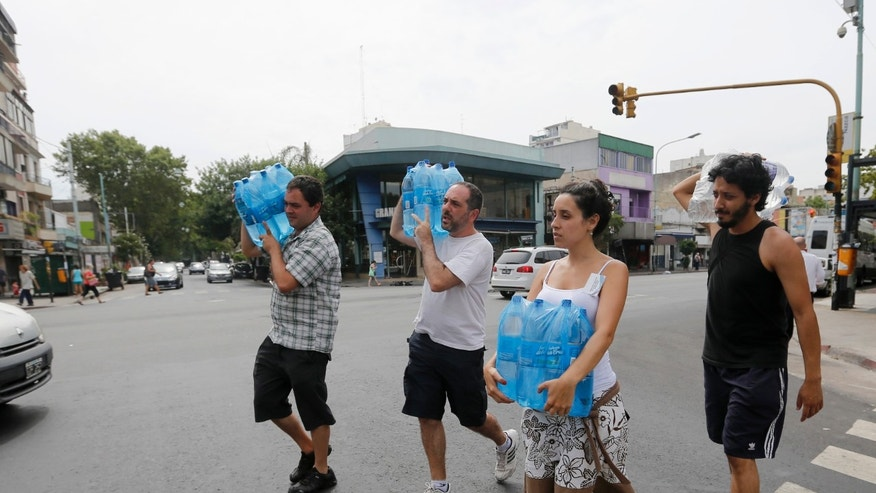 Residents carry packs of water during a heat wave that led to record electricity consumption in Buenos Aires December 30, 2013. With temperatures reaching 100 degrees, water and power outages blanket large swaths of Argentina's capital city, sparking protests and placing residents, particularly those in high-rise buildings, at risk. (REUTERS/Enrique Marcarian)