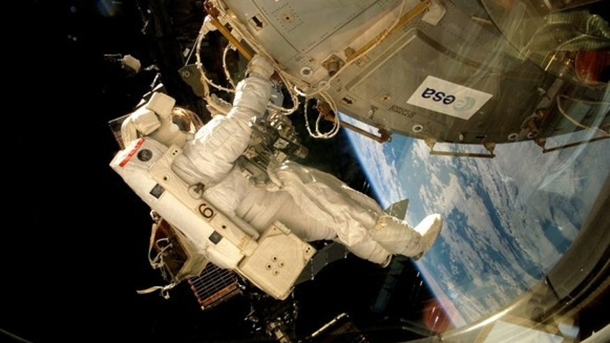 An astronaut fixes the EXPOSE-E platform onto the International Space Station. (ESA)