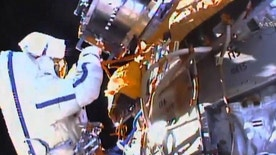 This photo taken from video provided by NASA shows Russian cosmonauts Yuri Malenchenko and Sergey Volkov install fresh experiments outside the International Space Station on Wednesday, Feb. 3, 2016. The spacewalkers set off to retrieve biological samples that have been outdoors seven years, and put out some new science trays. They also planned to test a new glue that might prove useful in years to come on the station's exterior. (NASA via AP)