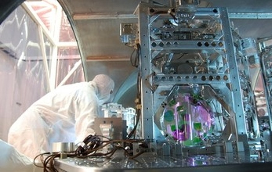 A technician works on one of LIGO's optics. At each observatory, the 2 1/2-mile long L-shaped LIGO interferometer uses laser light split into two beams that travel back and forth down the arms. The beams are used to monitor the distance between mirrors precisely positioned at the ends of the arms. According to Einstein's theory, the distance between the mirrors will change when a gravitational wave passed by the detector.