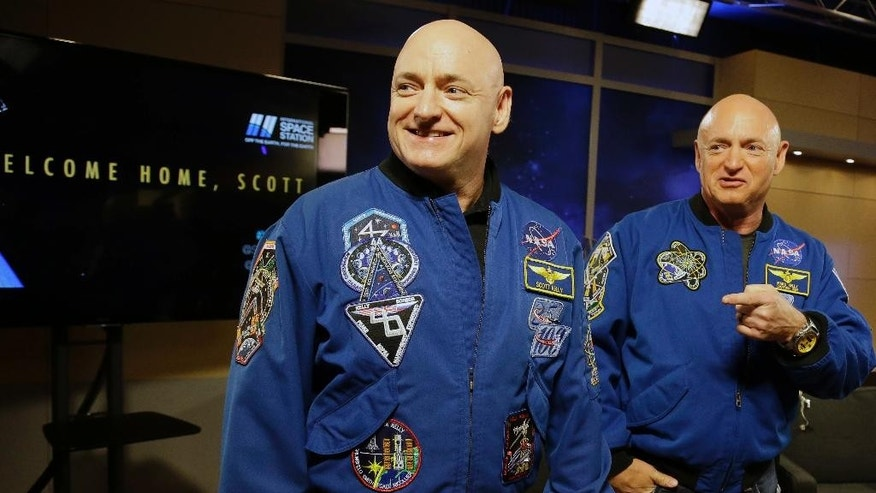 FILE - In this March 4, 2016, file photo, NASA astronaut Scott Kelly, left, and his twin Mark get together before a press conference in Houston. Scott Kelly set a U.S. record with his a 340-day mission to the International Space Station. Kelly is exploring lots of options for the next step in his life. But he's saving the serious job discussions for retirement, coming up April 1. His identical twin, Mark, retired as an astronaut soon after the shuttle program ended in 2011, yet agreed to medical testing as part of the unprecedented twins study that got under way well before Scott's March 2015 launch from Kazakhstan. (AP Photo/Pat Sullivan, File)