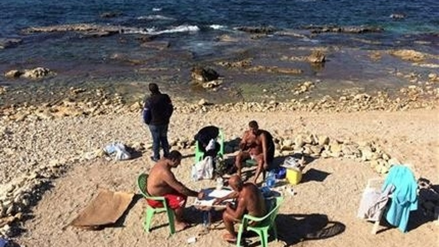 Lebanese men play cards and smoke water pipe, as they sunbath during unusually warm weather at the Mediterranean Sea off the Corniche, or waterfront promenade, in Beirut, Lebanon. Earth got so hot last month that federal scientists struggled to find words, describing temperatures as astronomical,staggering and strange.  (AP Photo/Hussein Malla)