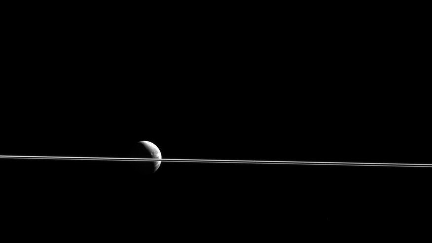 Dione appears cut in two by Saturn's razor-thin rings, seen nearly edge-on in a view from NASA's Cassini spacecraft. This scene was captured from just 0.02 degrees above the ring plane. (NASA/JPL-Caltech/Space Science Institute)