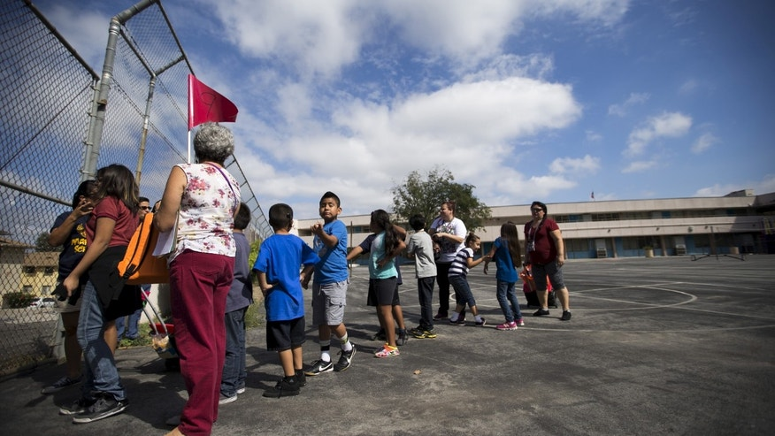 "A teacher holds a flag as she evacuates with her students during the ""Great ShakeOut"" earthquake drill at Marlton School in Los Angeles, California October 15, 2015. (REUTERS/Mario Anzuoni)"