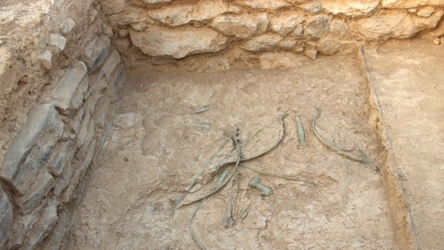 Bows, arrows, daggers and axes scattered on the ground at Mudhmar East, located on the coast of the Arabian Peninsula.