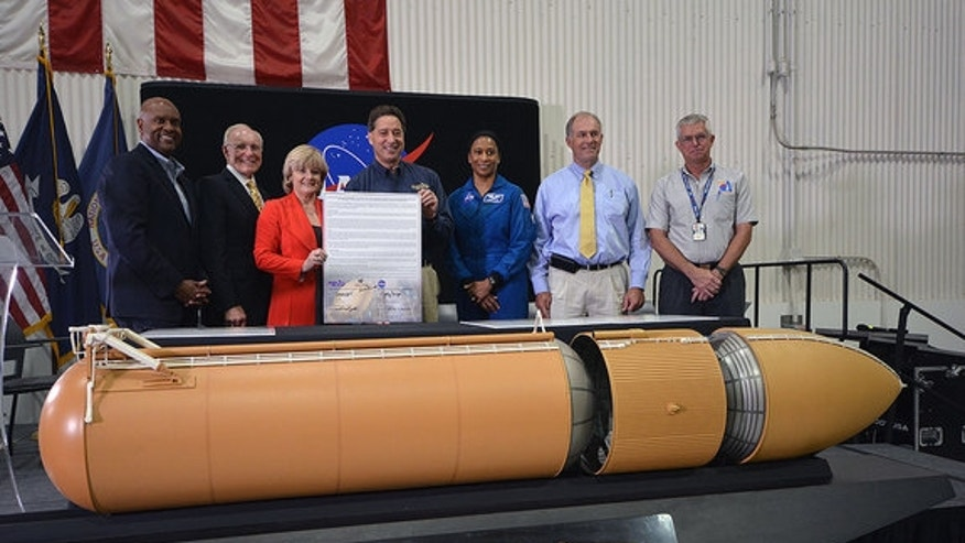NASA and California Science Center officials present a signed title transfer document for the last space shuttle external tank, ET-94, during a ceremony at the Michoud Assembly Facility on Tuesday, April 12, 2