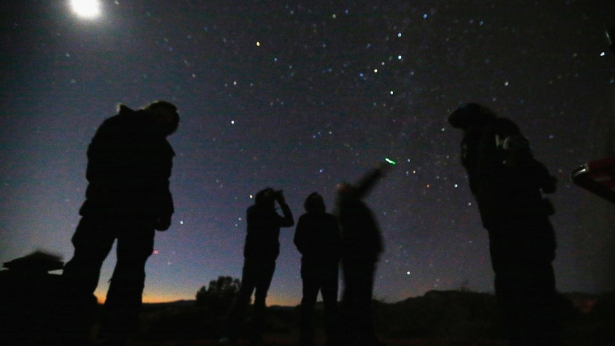 File photo - People look at the night sky using night vision goggles during an Unidentified Flying Object (UFO) tour in the desert outside Sedona, Arizona Feb. 14, 2013. (REUTERS/Mike Blake)