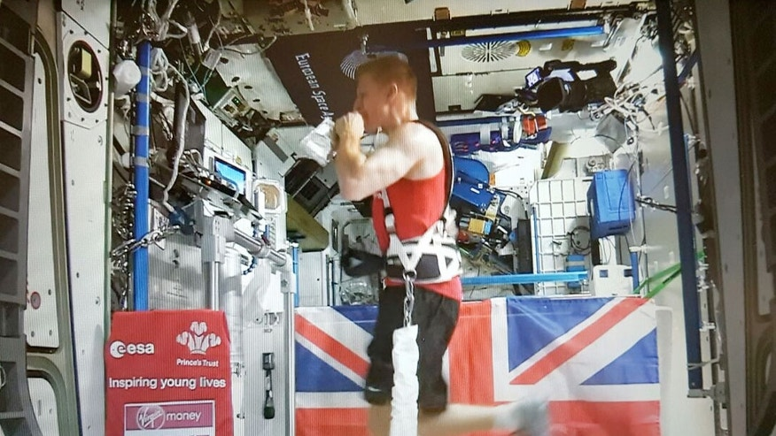 British astronaut Tim Peake of the European Space Agency (ESA) takes a drink while running the London Marathon aboard the space station on April 24, 2016.