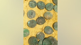 This photo made available by the City Council of Tomares on Friday, April 29, 2016, shows some of the bronze and silver-coated coins dating from the end of the 4th century Workers laying pipes in a southern Spanish park have unearthed a 600-kilogram (1,300-pound) trove of Roman coins in what culture officials say is a unique historic discovery. (City Council of Tomares via AP)