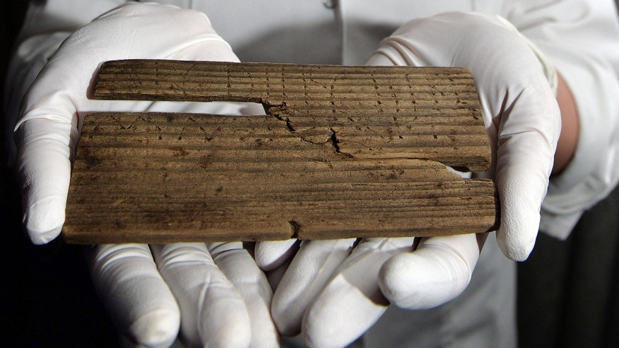 June 1, 2016: Luisa Duarte, a conservator for the Museum of London, holds a piece of wood with the Roman alphabet written on it.