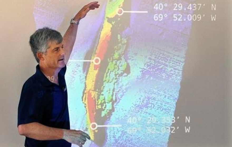 OceanGate CEO and co-founder Stockton Rush speaks in front of a projected image of the wreck of the ocean liner SS Andrea Doria during a presentation on Monday, June 13, 2016, in Boston, of findings after an undersea exploration earlier this month of the wreck in the Atlantic Ocean near Nantucket. The ship went down after a collision nearly 60 years ago, killing 46. (AP Photo/Bill Sikes)