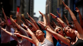 People participate in a yoga class during the 14th Annual Solstice in Times Square event in New York, U.S., June 20, 2016.  REUTERS/Shannon Stapleton - RTX2H7QT