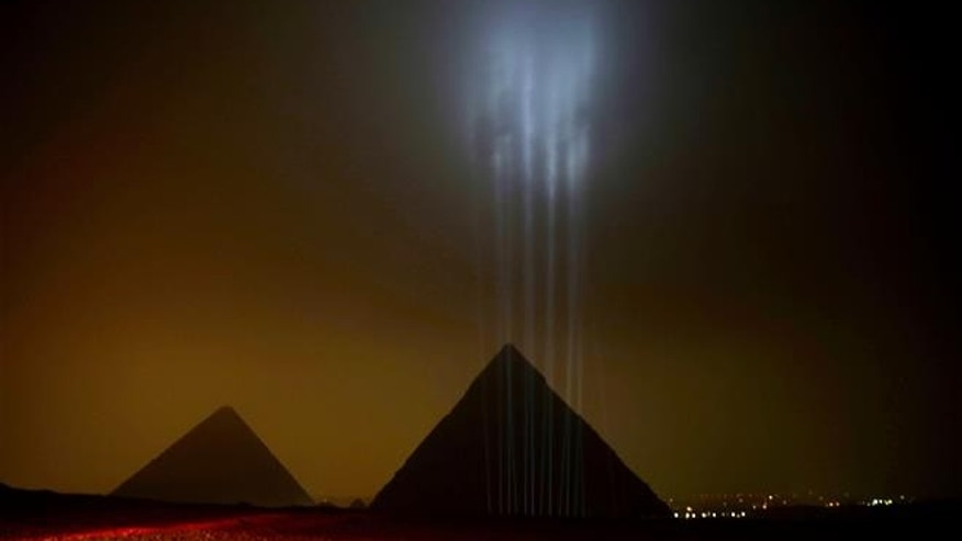 The Giza pyramids are backlit ahead of a New Year's Eve fireworks display near Cairo on Dec. 31, 2015.