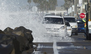 Drivers make their way along a beach road as a wave crashes onto the street due to a combination of high tides and high surf in Oceanside, California October 27, 2015.      REUTERS/Mike Blake - RTX1TIRD
