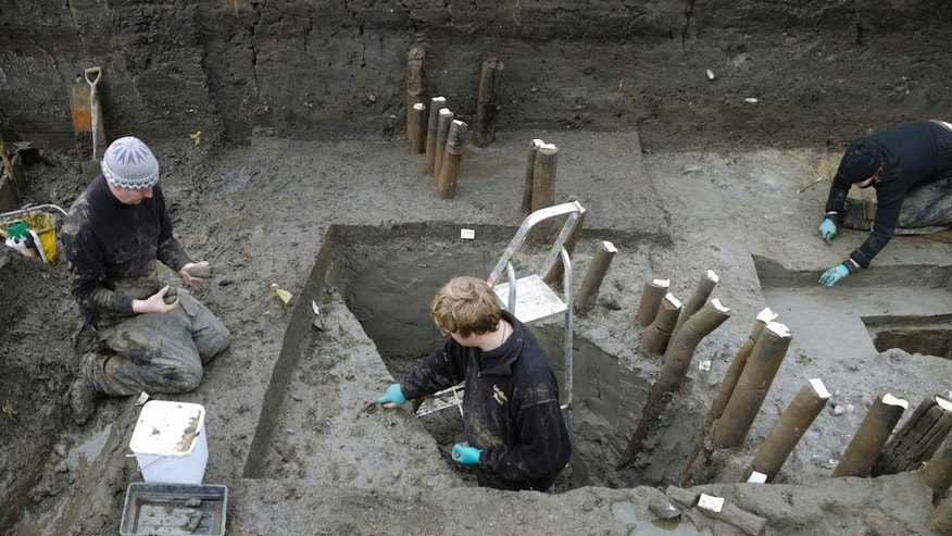 Archaeologists from the Cambridge University Archaeological Unit remove river silts to expose the wood of the Bronze Age settlement at Must Farm in the fenlands of eastern England.