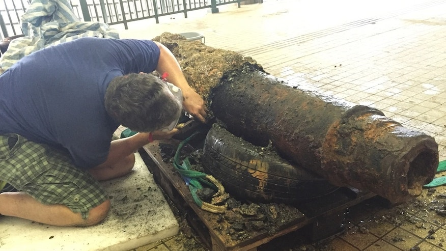 Paul Harrison, a conservator at the  Hong Kong Maritime Museum, removes centuries of seabed concretions from the cannon.