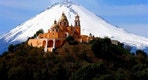 FILE - In this Nov. 21, 2006 file photo, the Our Lady of Remedios church is backdropped by the snowcapped volcano Popocatepetl, in Cholula, in the Mexican state of Puebla. The 150th anniversary of the Battle of Puebla, in which the U.S. helped Mexico combat the French occupation is being used as an anchor to get U.S. tourists to visit the 16th century colonial Mexican city. (AP Photo/Joel Merino, File)
