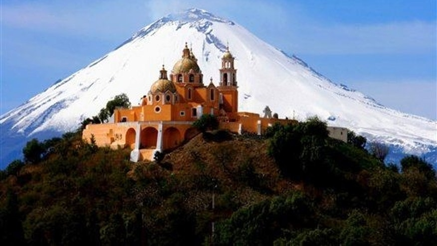 In this Nov. 21, 2006 file photo, the Our Lady of Remedios church is backdropped by the snowcapped volcano Popocatepetl, in Cholula, in the Mexican state of Puebla. It's perched atop an ancient pyramid.