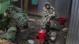 A woman collects water from a tube-well in Dhaka, Bangladesh, in April.