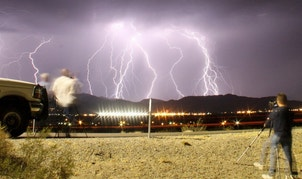 Southern California storm chasing photographers take pictures of the mass lightning bolts lighting up night skies from monsoon storms passing over the high deserts, early Wednesday north of Barstow, California, July 1, 2015. Picture taken using long exposure. REUTERS/Gene Blevins - RTX1ILCC