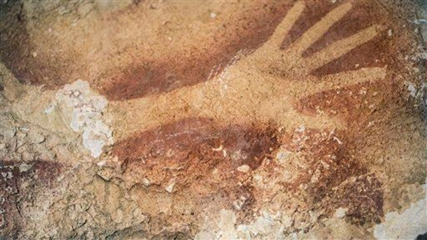 This undated handout photo provided by Nature Magazine shows stencils of hands in a cave in Indonesia.