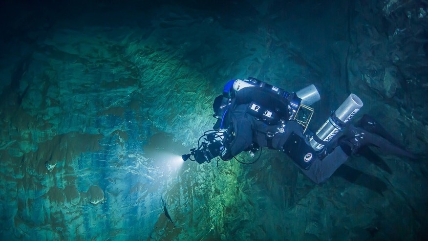 In this underwater photo taken Aug. 15, 2015 in the flooded Hranicka Propast, or Hranice Abyss, in the Czech Republic Polish explorer Slawomir Packo is exploring the limestone abyss and preparing for deeper exploration with the use of a remotely-operated underwater robot, or ROV. (Krzysztof Starnawski of EXPEDITION via AP)