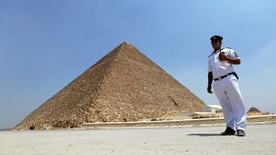 A policeman stands guard in front of the Pyramid of Khufu, the largest of the Great Pyramids of Giza, on the outskirts of Cairo, Egypt, August 31, 2016. Picture taken August 31, 2016. REUTERS/Mohamed Abd El Ghany - RTX2NS65
