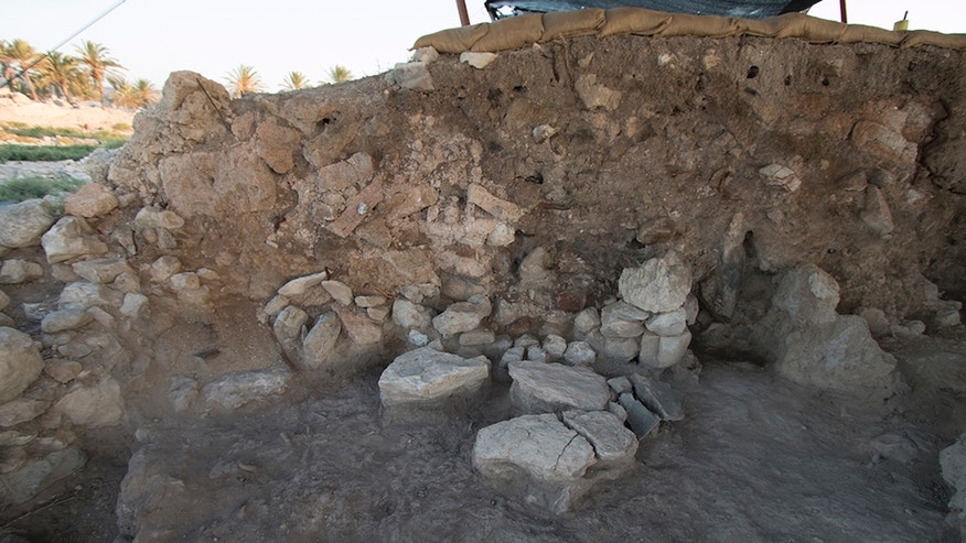 An excavated area at Tel Megiddo from 2014 shows a stone-paved floor that has fire-blackened sediment. The wall consists of collapsed red and yellowish mud bricks.