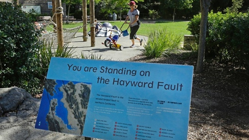 In this Tuesday, Oct. 18, 2016 photo, a sign notifying people they are standing on the Hayward Fault stands at the children's zoo area at the Oakland Zoo in Oakland, Calif.